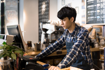 Young waiter using computer in coffee shop at checkout counter