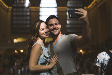 Happy young couple taking a selfie at the station