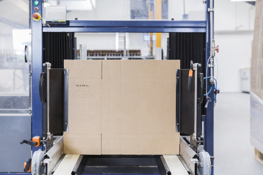 Cardboard being assembled by robot in a factory