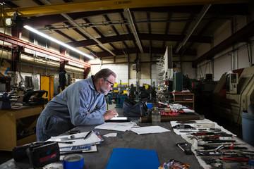 Mature factory worker leans over digital tablet