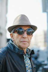 Headshot of a senior fashionable man with hat and sunglasses