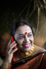 A middle aged woman taking and making conversation with mobile phone
