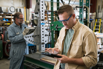 Factory worker looking at digital tablet with coworker in background