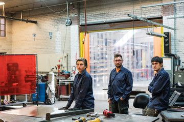 Team of three stand for portrait in metal factory