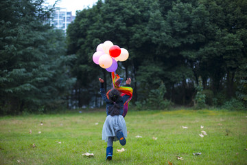 One little Girl playing with colorful balloon outdoor in the aut