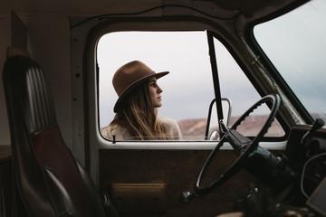 portrait of woman in hat through van window with view of interior