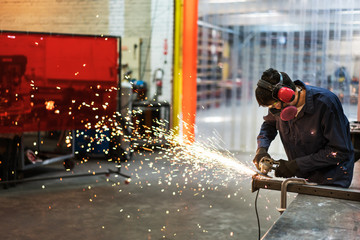 Young man creating sparks in a factory