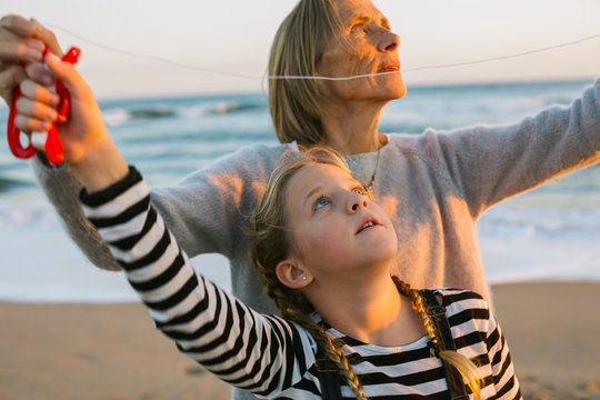Grandmother and her granddaughter flying a kite on the beach at sunset,
