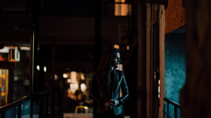 Attractive woman standing on the terrace at night