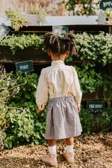 A little girl looking towards garden / plants