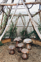 A wooden teepee with wooden mushrooms
