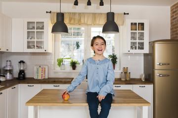 Cheerful little girl posing in kitchen.