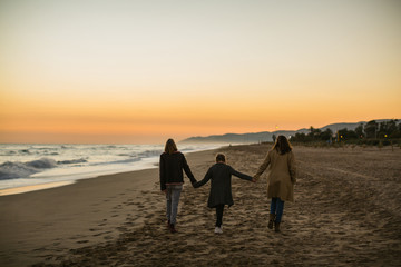 Back view of family enjoying the sunset on the beach in autumn.