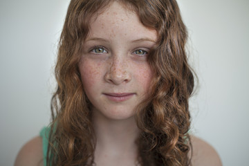 Portrait of a preteen girl with red hair and freckles.