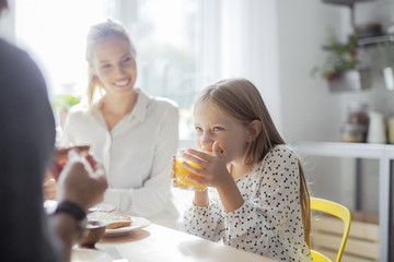 Cute Girl Drinking Juice and Having Breakfast With Her Parents