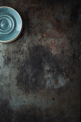 Dark metal background with a stack of saucers