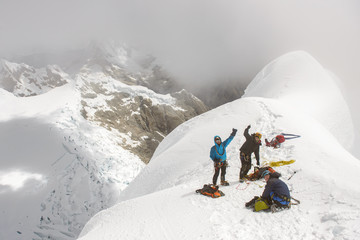 Mountain Climbers standing on top of Alpamayo Peak in Peru