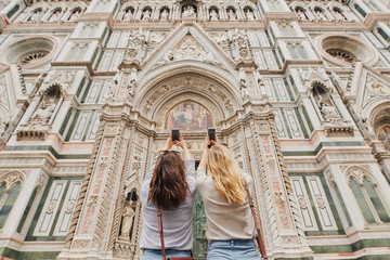Two girl friends photograph architecture buildings with smart ph