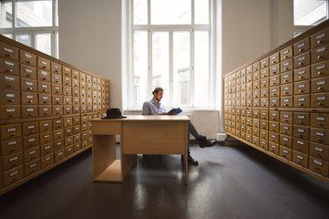 Student reading a book between index card drawers in public library