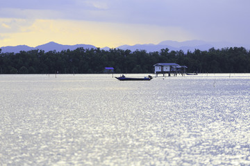 the small fishing house and a small fishing boat in the sea at the fish farm in Thailand