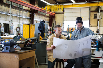 Two men in factory looking at blueprints