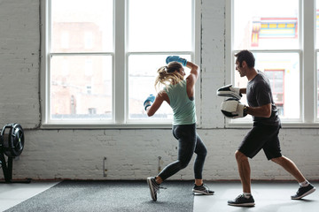 Strong, healthy woman working out in gym - boxing with trainer