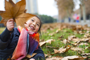One Little Girl Playing with leaf Outdoor in the Autumn day