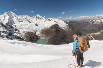 Male climber with big and heavy backpack standing in front of  a beautiful mountain range