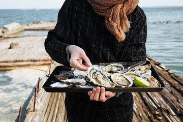 Young woman holding metal tray of open oysters ready for consuming on sea shore, outdoor