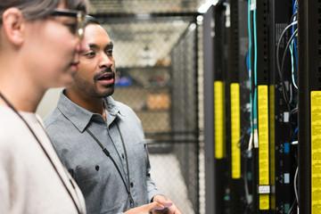 Two server room technicians talking