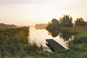 A empty pier in a small lake or pont, surrounded by grassland.