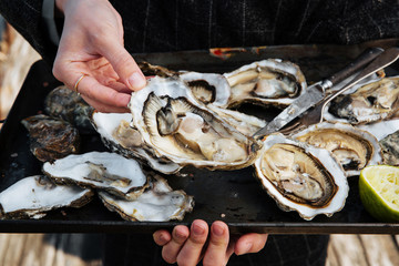 Woman holding metal tray of open oysters ready for consuming, outdoor, close up