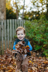 Cute young boy running with a pile of leaves in his hands