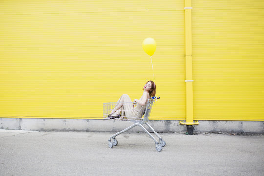 Young woman standing against a yellow wall and holding the balloon