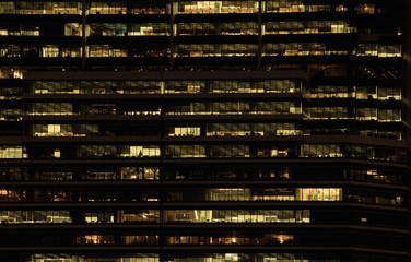 office building at night. Late night at work. Glass curtain wall office building