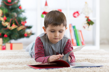 Cute child boy reading a book in front of the christmas tree, christmas time