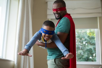 Son and father pretending to be a superhero at home