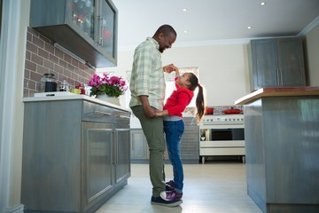 Father and daughter dancing together in kitchen