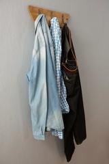 Jeans, denim jacket and shirt hanging on hook
