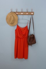 Red dress, hat and bag hanging on hook