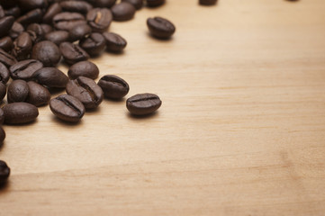 Coffee beans on the wooden board.Close up shot with selective focus.