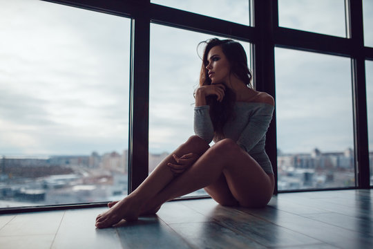 Sexy woman in gray bodysuit sits on the floor near the panoramic window.