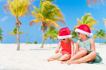 Adorable little kids have fun in Santa hat during Christmas beach vacation. New Year on the beach
