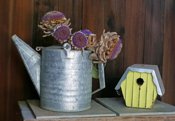 Alte Gießkanne aus Blech mit Trockenblumen und ein gelbes Vogelhaus