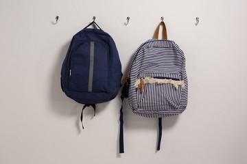 Schoolbags hanging on hook