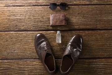 Shoes, perfume, wallet and sunglasses on wooden plank