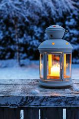 Lantern in garden, winter evening.