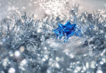 Silver and blue Christmas decorations on an abstract bokeh fairy lights blurred background