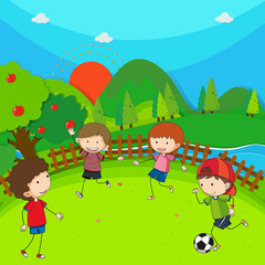 Four children playing football in the park