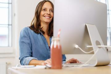 frau sitzt am schreibtisch und arbeitet am computer